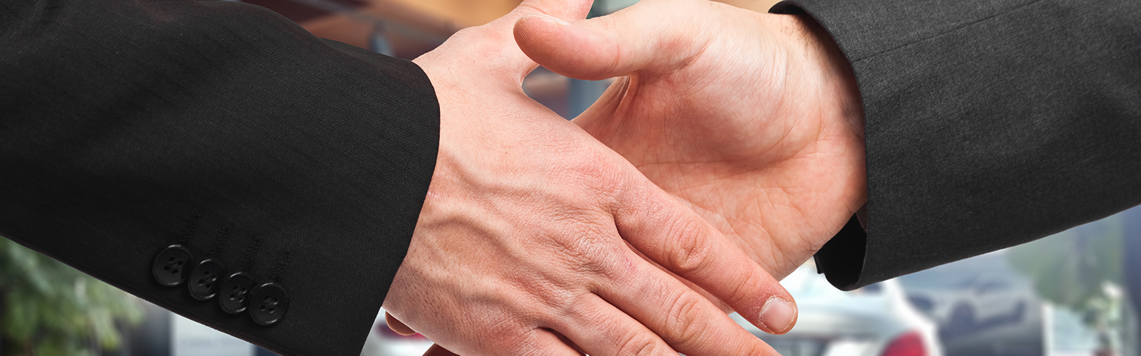 Close up of two men in suits shaking hands