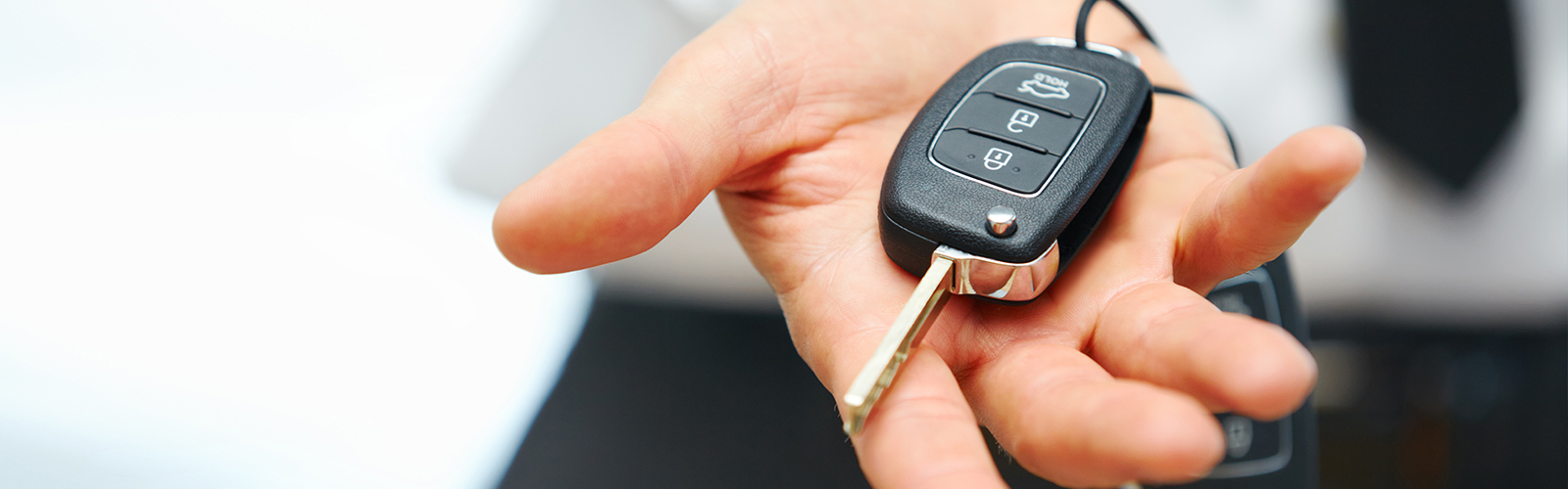 Person holding the keys to a new car in the palm of their hand.