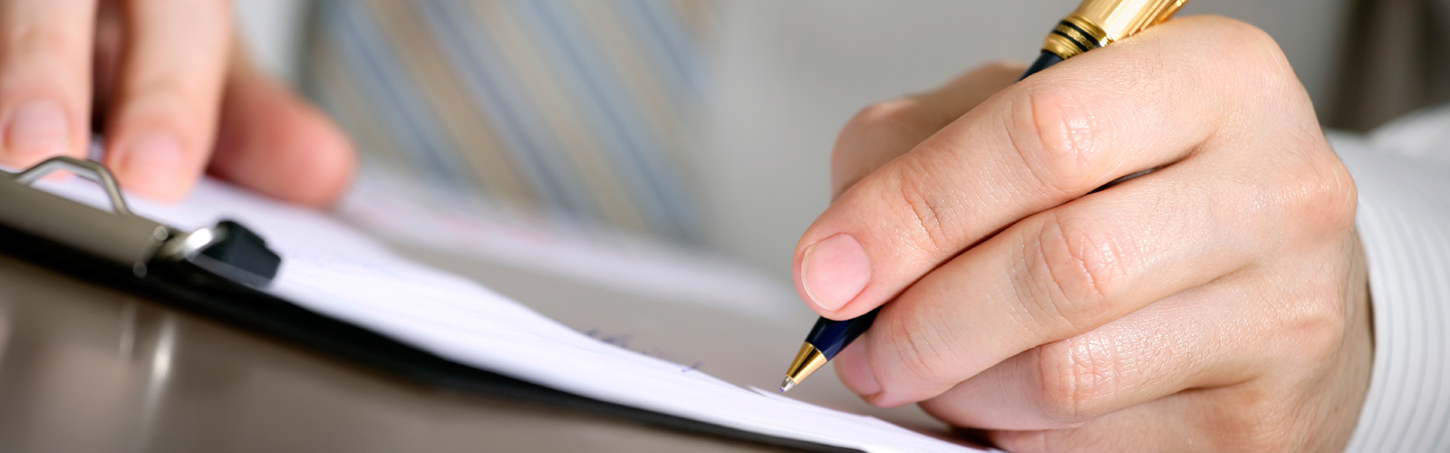 Close up of a man signing a finance contract on a new car at Norris Motor Group Brisbane.