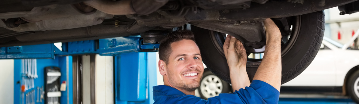 Smiling mechanic servicing the brakes on a car at Redcliffe Mitsubishi Brisbane.
