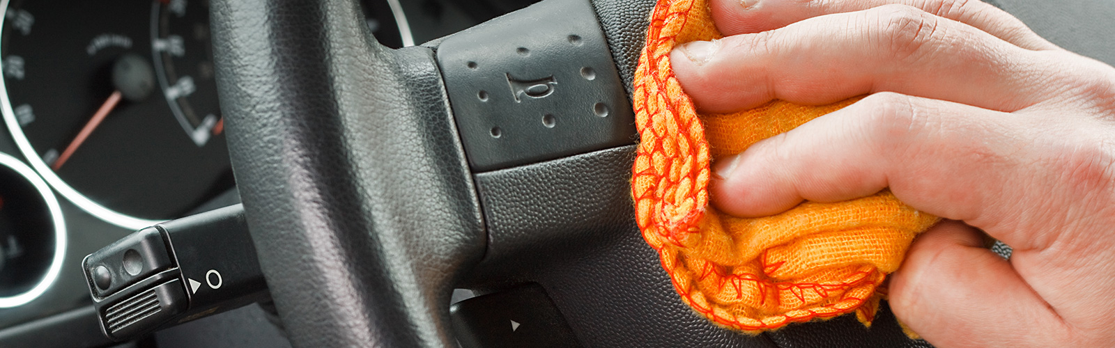 Detailer cleaning the steering wheel on a used car from Metro Used Cars in Brisbane.