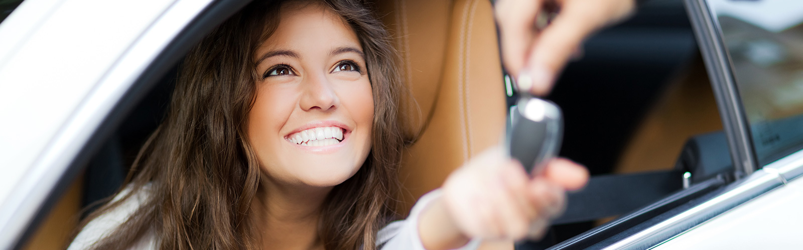 Smiling girl getting the keys to her new car at Metro Used Cars In Brisbane.