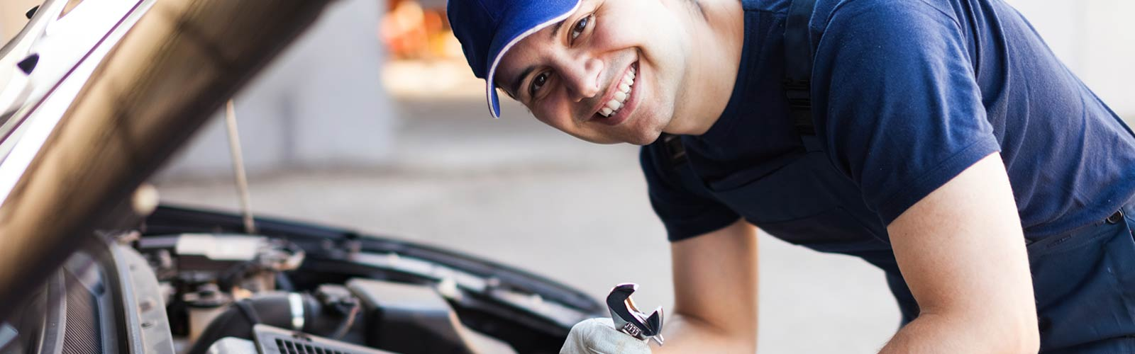 Smiling mechanic servicing the engine on a car at one of eight NMG service centres in Brisbane.